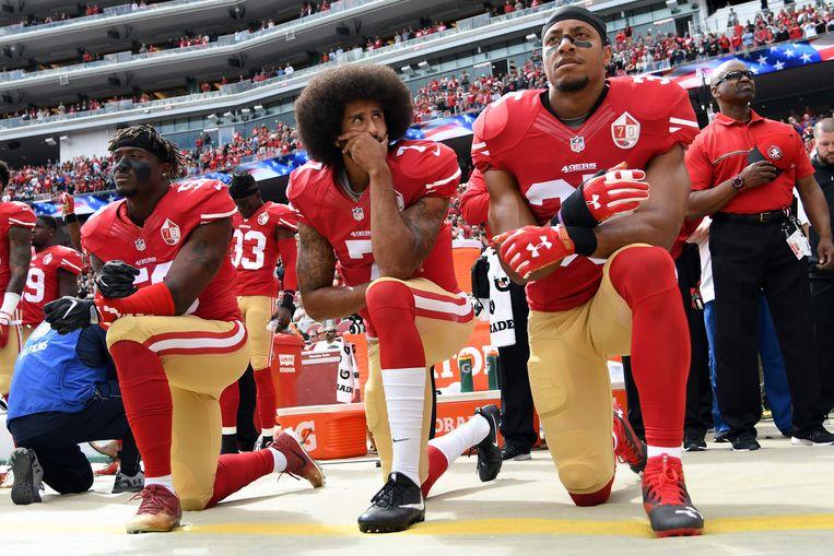 Archiefbeeld: vlnr.: Eli Harold, Colin Kaepernick en Eric Reid als spelers van de San Francisco 49ers knielen aan de zijlijn tijdens het Amerikaanse volkslied vlak voor de wedstrijd tegen de Dallas Cowboys in 2016.  Beeld AFP