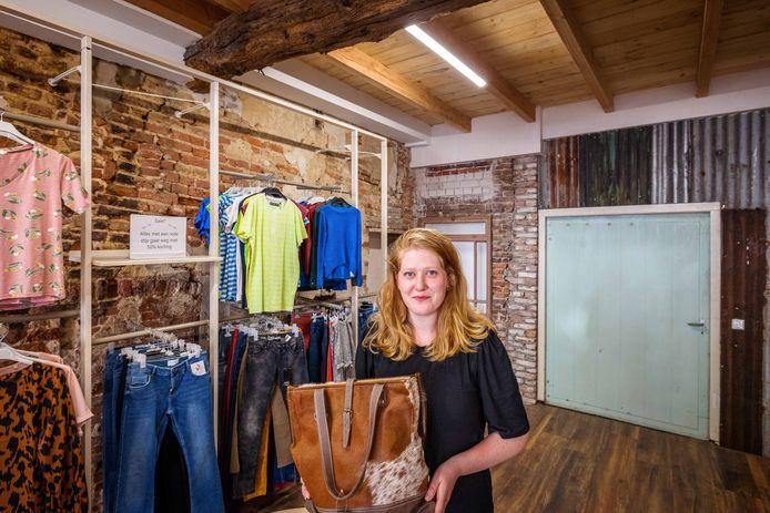 Tamara van der Woude tussen de kledingrekken in haar nieuwe kledingwinkel Bij Juulsz, met aan de binnenzijde zichtbaar de oude muren.