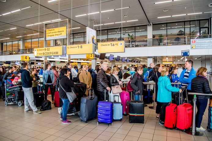 Reizigers wachten in rijen voor de check-ins en security check op luchthaven Schiphol.