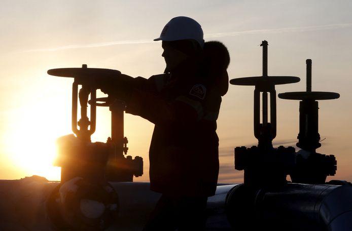 Een werknemer controleert de kleppen van een pijplijn op een Russisch olieveld