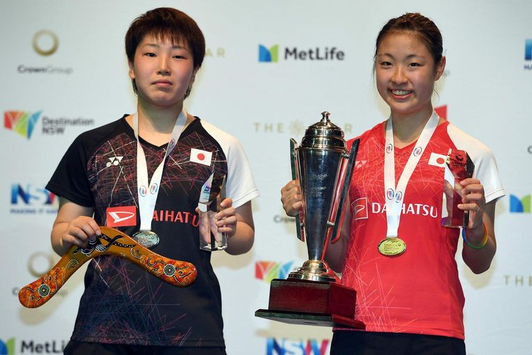 Nozomi Okuhara of Japan (R) holds the winner's trophy after defeating compatriot Akane Yamaguchi in the Australian Open women's singles badminton final in Sydney on June 25, 2017. / AFP PHOTO / William WEST Beeld afp