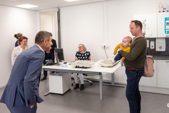Staatssecretaris Paul Blokhuis begroet baby Job en zijn vader bij het bezoek aan het consultatiebureau van de jeugdgezondheidszorg van de GGD.