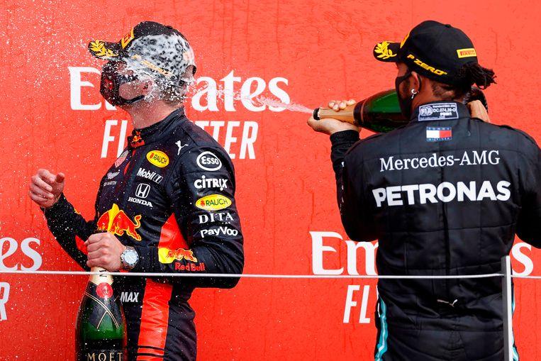 Max Verstappen krijgt een champagnedouche van Lewis Hamilton, die toch te verslaan blijkt. Beeld AFP