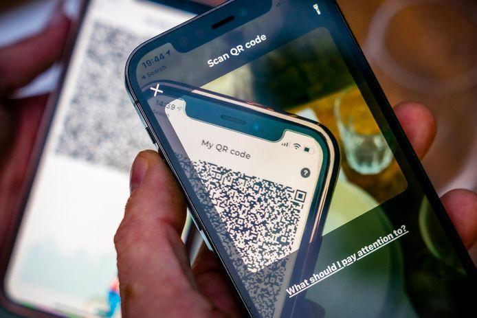 Een mobiele telefoon met de QR-code van de CoronaCheck App.