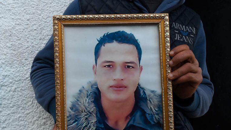 Walid Amri poseert met een portret van zijn broertje Anis voor hun ouderlijk huis in het Tunesische dorp Oueslatia. Beeld anp