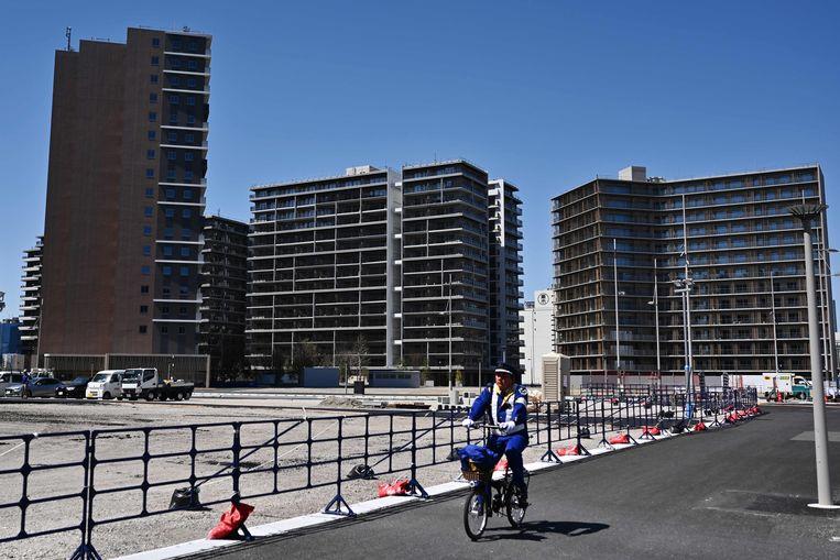 Een man fietst voorbij het olympisch dorp in de baai van Tokio. In de 5.600 appartementen moeten de 11.000 atleten logeren tijdens de Spelen. Beeld AFP