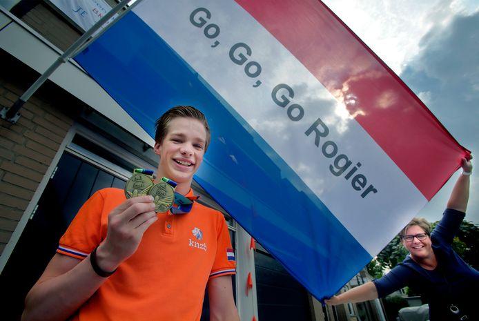 Rogier is blij met zijn twee bronzen medailles. Ook moeder Marjan is trots. Zij hing een spandoek op en stak de vlag uit.