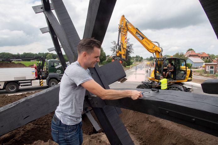 Jan Willem ten Beitel kwast het laatste stukje van het grote waterrad zwart. Het kunstwerk is maandagochtend geplaatst op nieuwe rotonde Haaksbergseweg / N315.