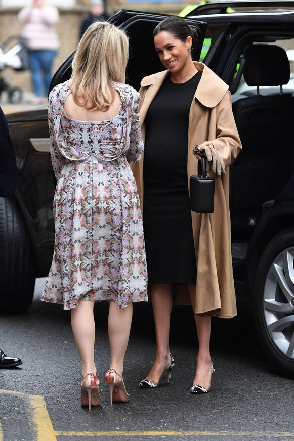 Meghan draagt hier een zwarte jurk van Hatch, een camelkleurige jas van het Italiaanse modehuis Oscar de la Renta en hakken van Gianvito Rossi.