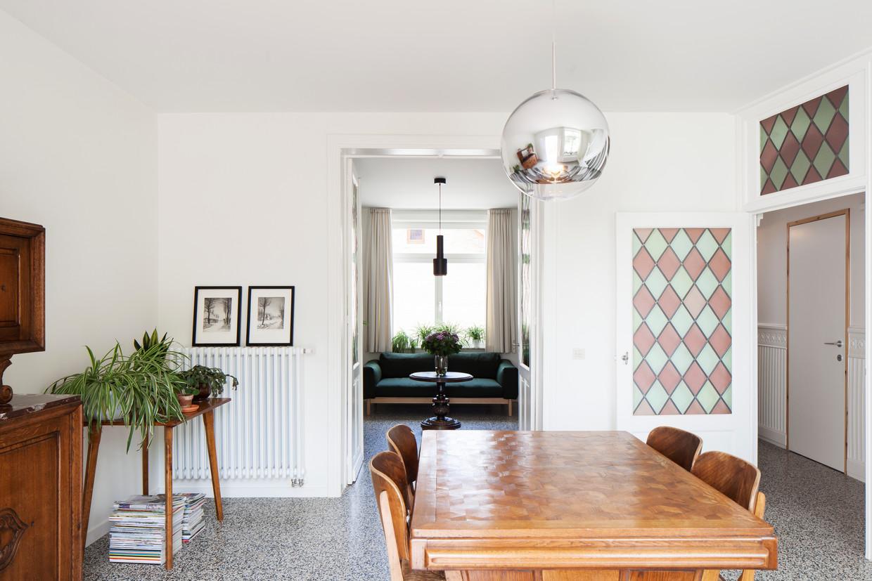 De vroegere meubels komen nog mooier tot hun recht in het hedendaagse interieur met witte muren en zwarte terrazzotegels.  Beeld Johnny Umans
