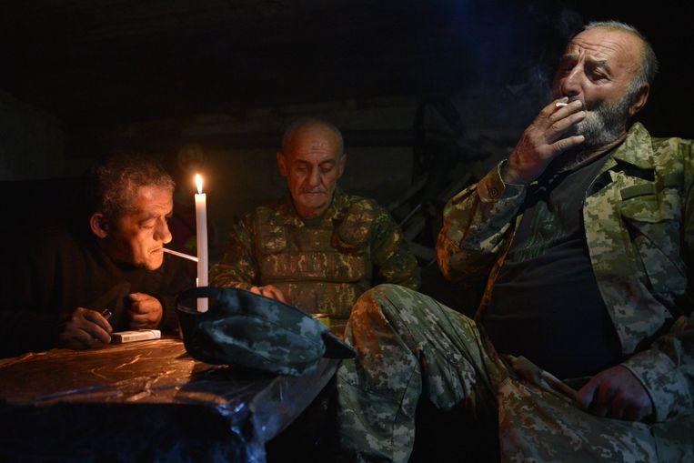 Militaire vrijwilligers schuilen in een kelder van een appartementencomplex in Nagorno-Karabach. Beeld AFP