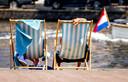 Mensen liggen in een strandstoel bij de Kattensloot in Amsterdam op een bloedhete dag in juli tijdens de eerste hittegolf in drie jaar tijd.