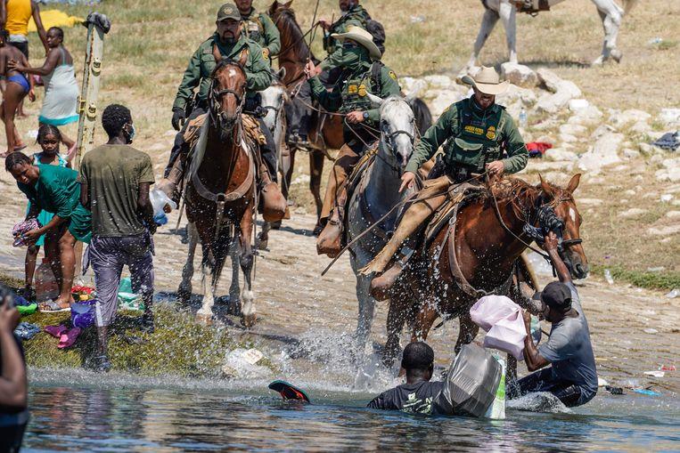 Amerikaanse grenswachten jagen Haïtiaanse vluchtelingen terug over de grens.  Beeld AFP