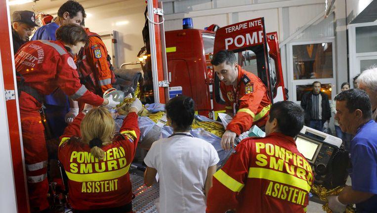 Gewonden van de brand in een club in Boekarest worden naar het ziekenhuis gebracht. Beeld epa