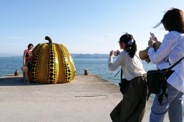 De bestipte pompoen van Yayoi Kusama op het Japanse eiland Naoshima is een trekpleister voor toeristen die er massaal selfies maken. Beeld Robin Broos
