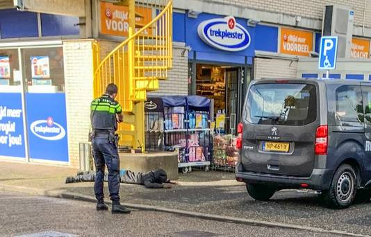 Eén van de overvallers werd even voor zijn arrestatie liggend op zijn buik onder schot gehouden door een politieagent.