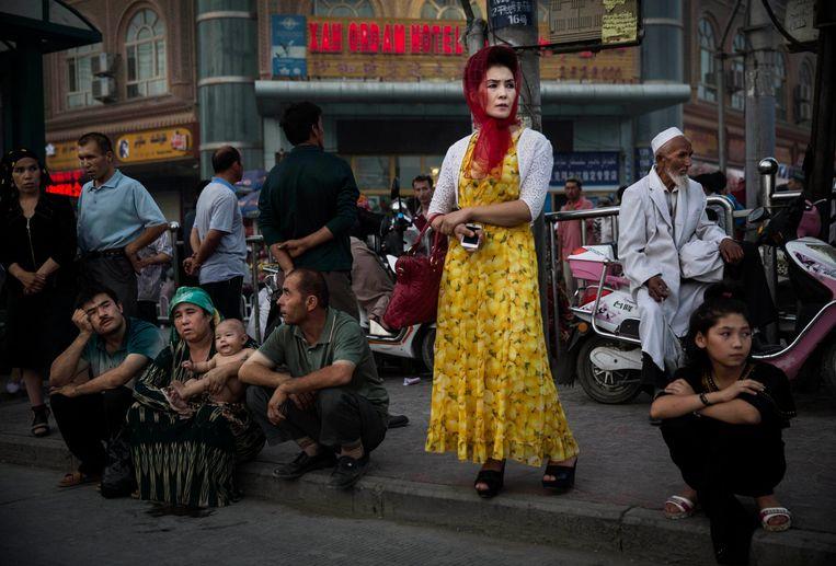 Oeigoeren wachten op de bus in Kashgar, Xinjiang. Beeld Getty Images