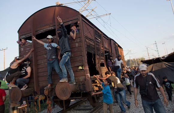 Migranten duwen een treinwagen naar het politiekordon.