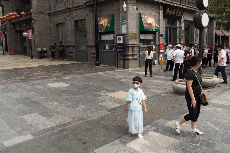 Restaurantmedewerkers in de toeristenbuurt Dashilan in Peking worden opgetrommeld om een virustest af te leggen. Beeld Ruben Lundgren