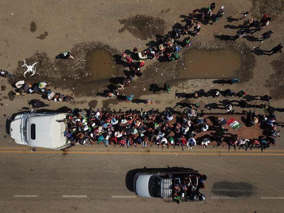 Deelnemers aan de migrantenkaravaan bevinden zich in Mexico en rijden even mee met een vrachtwagenoplegger.