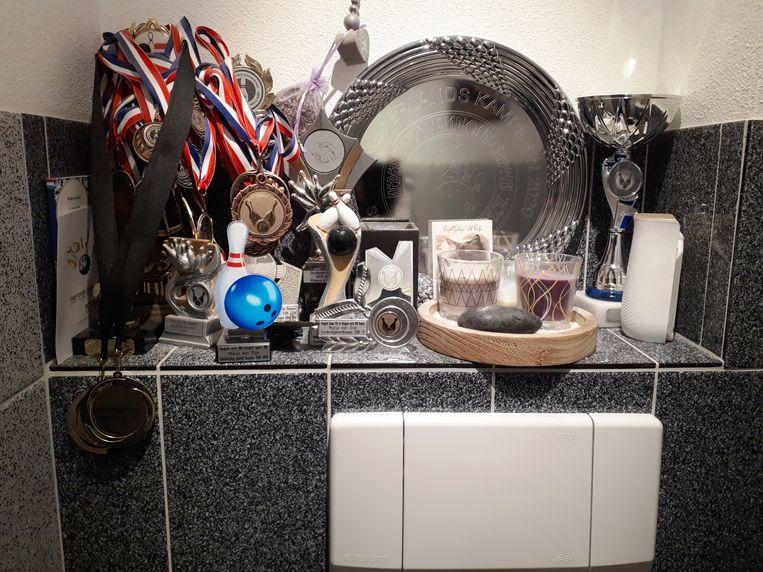 De prijzen van bowlingkampioene Marja van Dijk, boven de wc. Beeld Emiel Hakkenes