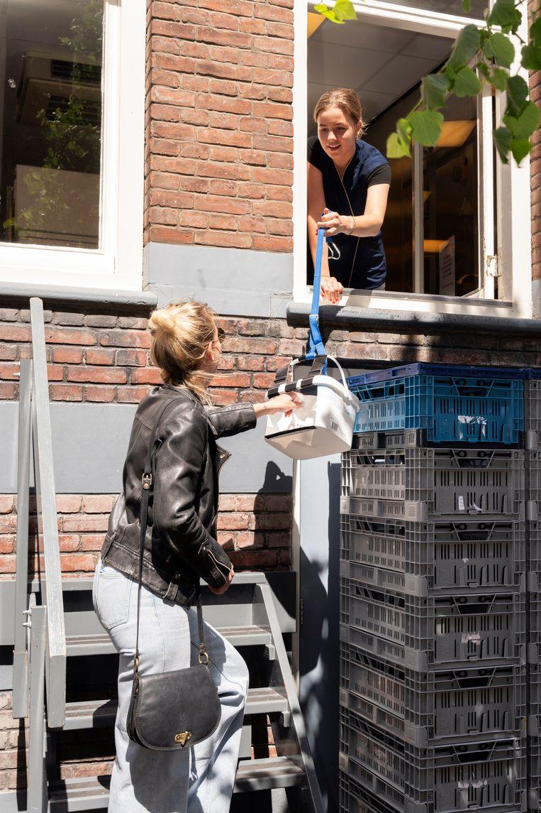 Kleindochter Stella geeft de kroketten in een mandje aan de klant. Beeld Els Zweerink