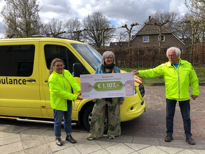 Anne-Marie van Orsouw overhandigt de cheque aan Nicole Jorna en Barry van Brakel van Stichting WensAmbulance. De ambulance kwam voorrijden bij haar thuis in Heesch.