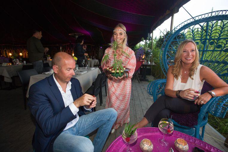 De klanten genieten van de gerechten in een tent middenin een grote wietplantage.