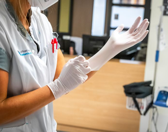 Verplegend en verzorgend personeel, zoals hier in het Catharina Ziekenhuis in Eindhoven, moet nog steeds doorwerken met mondkapjes en beschermende kleding.