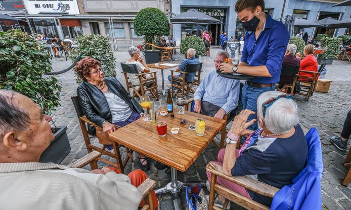 Een ober -met mondmasker- bedient de klanten op de Grote Markt van Kortrijk. Een beeld dat we de komende dagen nog vaak hopen te zien.