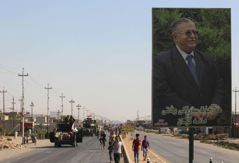 Een portret van de oud-Iraakse president Jalal Talabani langs de weg terwijl Iraakse troepen op weg zijn naar Kirkuk. Beeld AFP