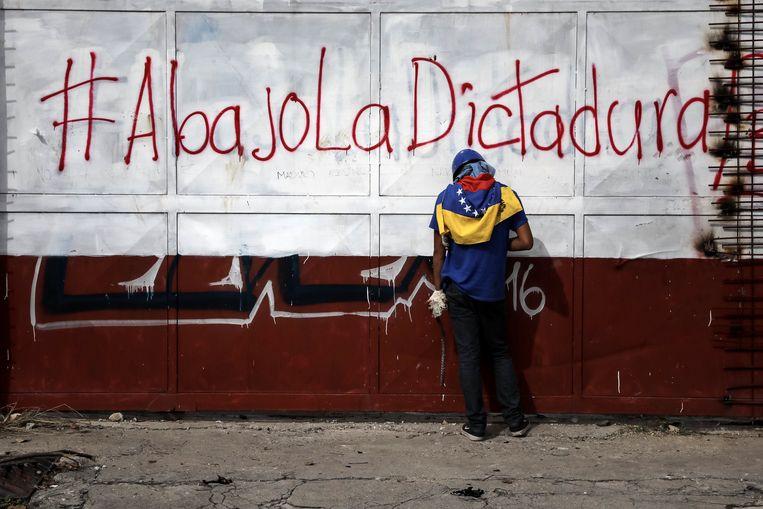 'Weg met de dictatuur' staat er te lezen op de muur achter de demonstrant die een steen in zijn hand houdt. Beeld epa