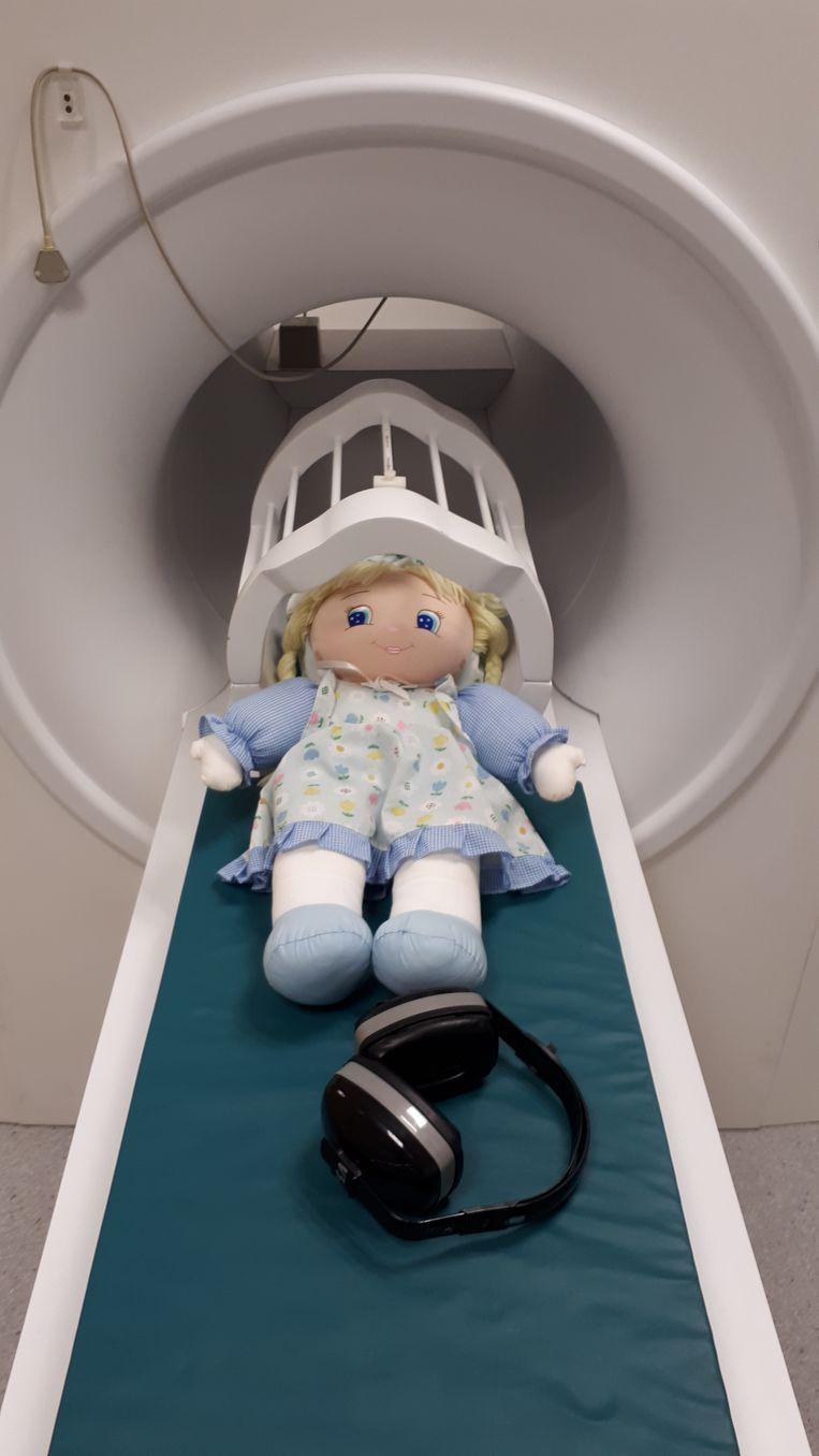 In het UZ Gent kunnen kinderen samen met hun knuffel oefenen in een dummy-MRI. Een koptelefoon simuleert de geluiden van een echte scanner.  Beeld UZ Gent