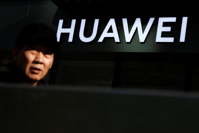 Een man loopt voorbij een Huawei-winkel in Peking.