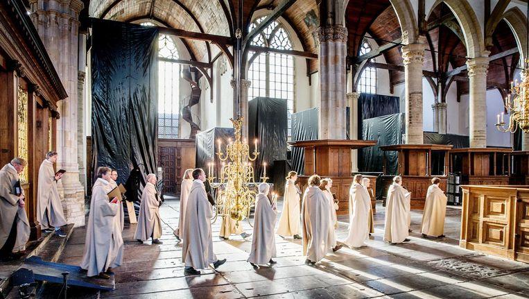 Kerkgangers in de Oude Kerk met op de achtergrond de in zwart plastic gehulde installaties van Christian Boltanski Beeld Jean-Pierre Jans