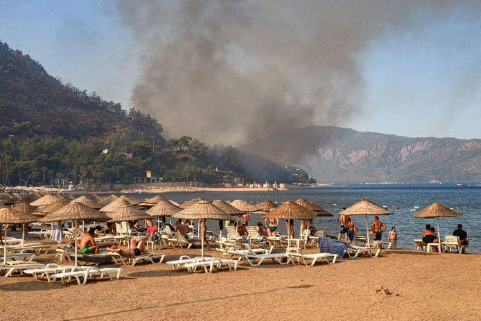 Toeristen kijken vanop het strand naar een bosbrand even verderop, aan de zuidkust van Turkije.