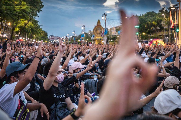 Zeker tienduizend Thai demonstreren zondag in Bangkok. Betogers maken een gebaar met drie vingers uit de reeks 'The Hunger Games'. Beeld Getty