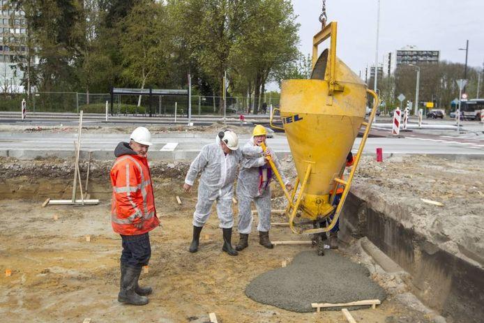 Wethouder Visscher en Ton de Lange van Winkelcentrum Woensel storten het eerste beton voor het nieuwe busstation.