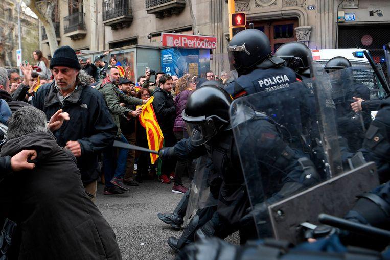 De oproerpolitie slaat betogers terug bij de zetel van de Spaanse regering in Barcelona. Beeld AFP