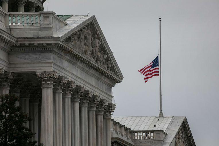 De Amerikaanse vlag hangt halfstok op het Capitool, om de dood te herdenken van politieman Brian Sicknick die omkwam toen een meute Trump-aanhangers het parlementsgebouw bestormden. Beeld AFP