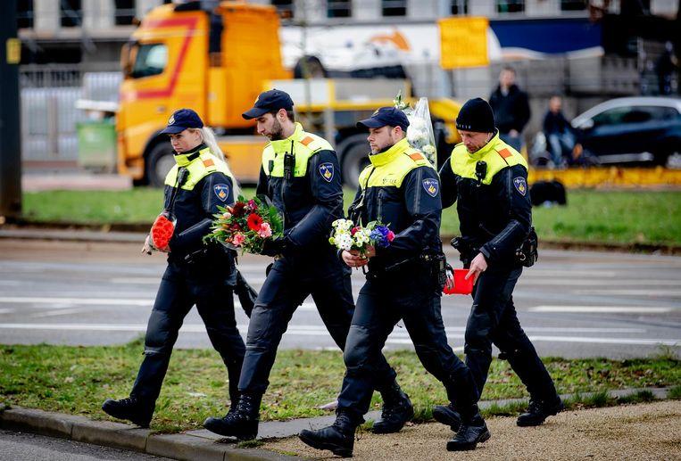 Politiemensen verplaatsen bloemen naar een verkeersveilige plek op het 24 Oktoberplein Beeld ANP