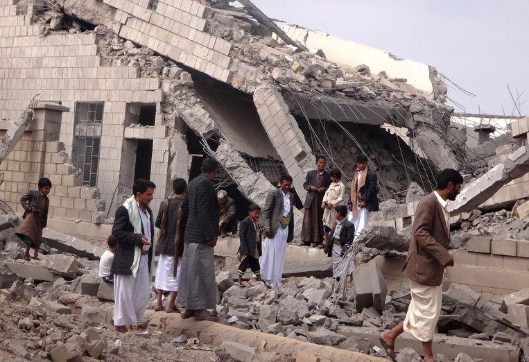 Mannen inspecteren een schoolgebouw na een luchtaanval. Beeld afp