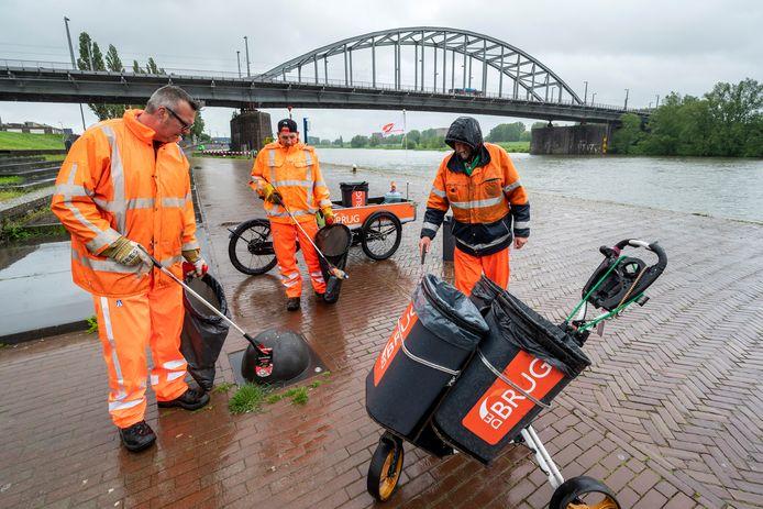 Een  ochtendploeg van De Brug in actie bij de John Frostbrug in Arnhem. Links begeleider Kees Nijdam, rechts daarvan de deelnemers Jan en Cees.