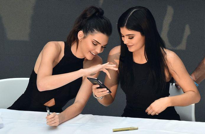Kendall en Kylie Jenner op hun telefoon.