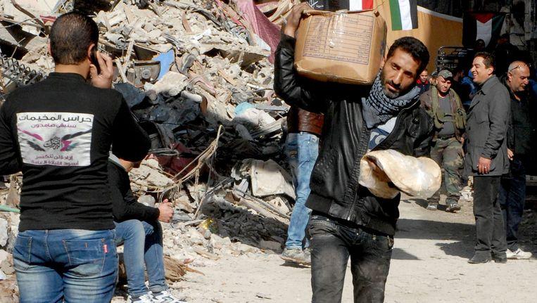 Een inwoner van Yarmouk draagt levensmiddelen met zich mee. Beeld EPA