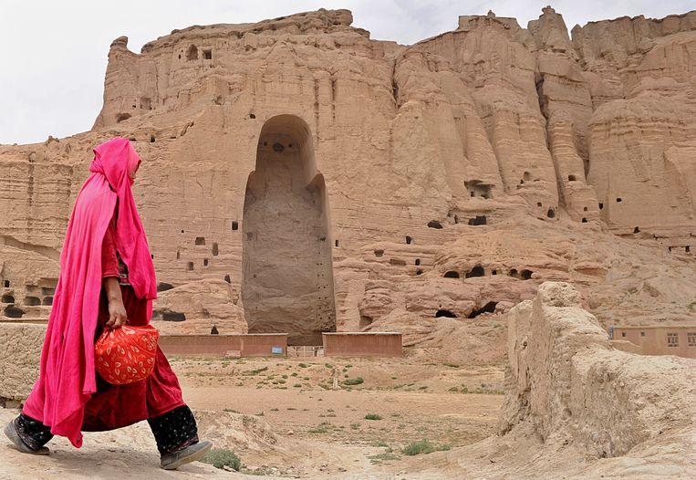 Een vrouw loopt langs de plek waar eens de grote staande Boeddha stond, die door de Taliban is opgeblazen. Beeld AFP