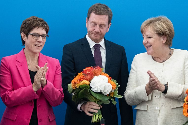 Michael Kretschmer krijgt na zijn winst bloemen van Angela Merkel en Annegret Kramp-Karrenbauer.  Beeld null