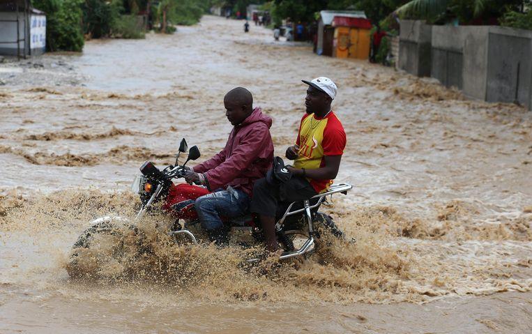 Mannen op een motorfiets steken een overstroomde straat over in Grand Goave. Beeld EPA