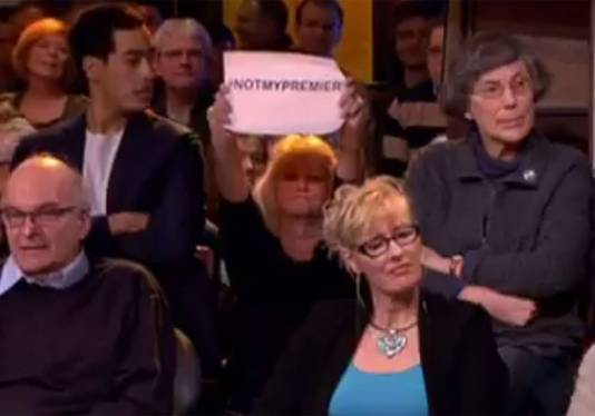 Een vrouw in het publiek houdt een briefje omhoog met #notmypremier.