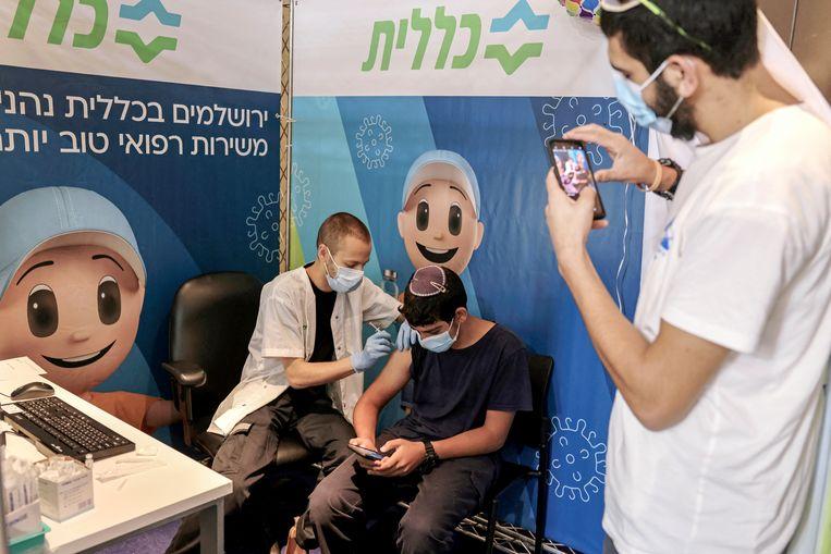 Een jonge Israelier krijgt een dosis Pfizer toegediend. Beeld Menahem Kahana / AFP